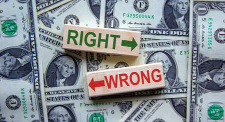 Right way vs wrong way, improvement and change management business concept. Words 'right, wrong' on wooden blocks on a beautiful background from dollar bills. Business concept.
