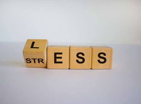 Having less stress or being stress-less. The word 'STRESS' and 'LESS' on wooden cubes. Beautiful white background, copy space.