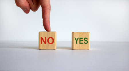 Hand making a choice between two cubes with words 'No' and 'Yes' on white background. Business concept. Copy space.
