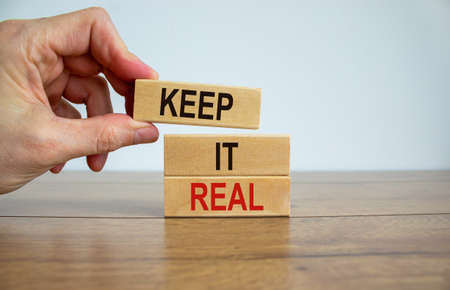 Male hand placing a blocks with word 'keep' on top of a blocks tower with words 'it real'. Wooden table. Beautiful white background. Copy space. Business concept. Standard-Bild