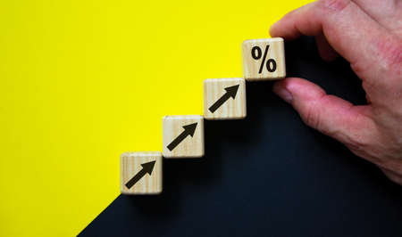 Business concept growth success process. Wood block stacking as step stair on paper yellow and black background, copy space. Male hand. Imagens