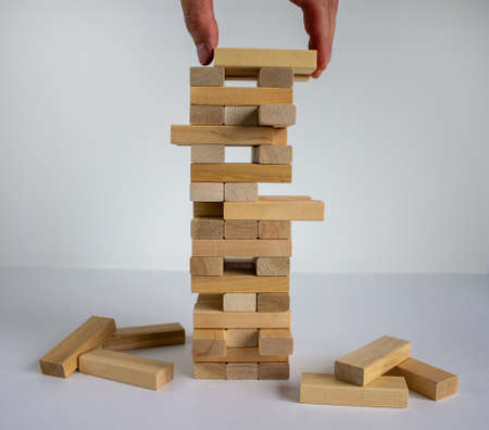 Wood block tower with architecture model. Concept Risk of management and strategy plan, growth business success process and team work. Male hand. Beautiful white background, copy space.
