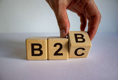 Business to Business or Busness to Consumer. Hand turns a cube and changes the expression 'B2B' to 'B2C' or vice versa. Business concept. Beautiful white background, copy space.
