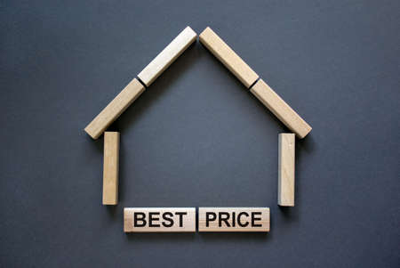 Model of a wooden house from wooden blocks. Words 'best price'. Copy space. Business concept. Beautiful gray background.