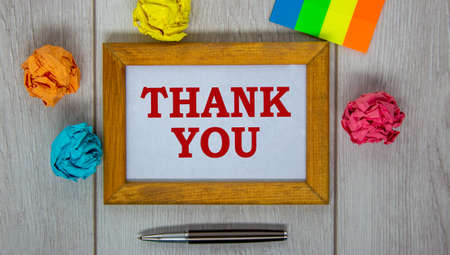 Wooden frame with inscription 'thank you' on beautiful wooden table, colored paper, metalic pen. Concept.