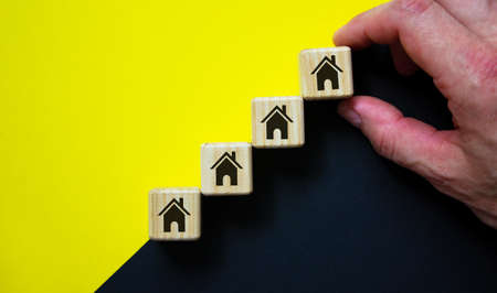 Business concept growth success process. Wood block stacking as step stair on paper yellow and black background, copy space. House icon. Male hand. Imagens