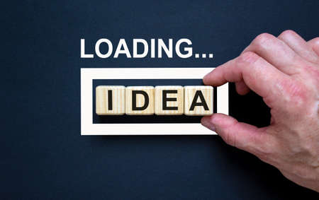 Loading word 'idea' with hand putting wood cube in progress bar. Business concept.