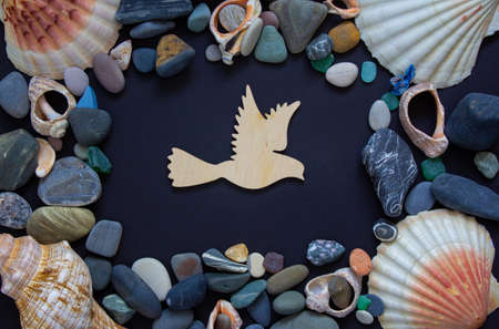 Wooden bird on a beautiful black background. Sea stones and seashells. Concept.