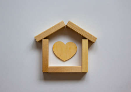 Wooden model of house from blocks. Heart sign. Place for your text. White background. Business concept.