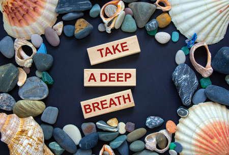 Text 'take a deep breath' on wooden blocks on a beautiful black background. Sea stones and seashells. Concept. Archivio Fotografico