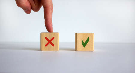 Hand making a choice between two cubes with No and Yes signs on neutral background. Business concept, copy space.