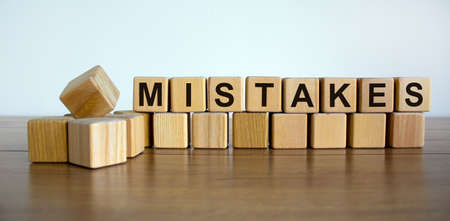 Concept word 'mistakes' on wooden cubes on a beautiful white background. Wooden table. Copy space. Business concept.