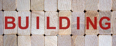 Wooden blocks form the word 'building'. Beautiful wooden background.
