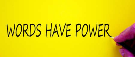 Hand writing 'words have power', isolated on yellow background. Business concept.