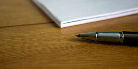 White notebook and pen on wood table. Business concept.
