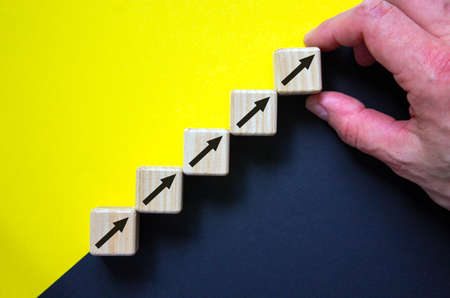 Business concept growth success process. Wood block stacking as step stair on paper yellow and black background, male hand. Copy space.