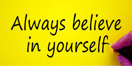 Hand writing 'always believe in yourself', isolated on yellow background. Business concept.