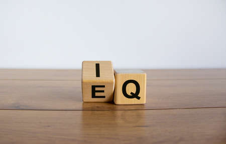 Wooden cubes with the expression 'IQ' 'Intelligence Quotient' to 'EQ' 'Emotional Intelligence Quotient'. Wooden table. Business concept, copy space. Beautiful white background.