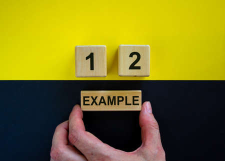 Businessman holds a block with word 'example'. Wooden cubes with numbers 1 and 2. Beautiful yellow and black background. Copy space. Concept of choice. Archivio Fotografico