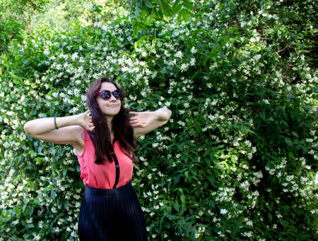 Young girl in sunglasses on a background of green bushes with flowers. A girl dressed in a pink blouse and a black skirt stands with her hands near her head. 免版税图像