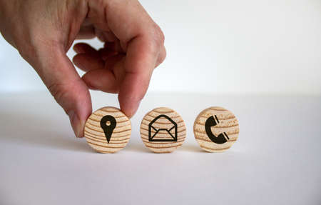 Customer contact and service conceptual image. Male hand holds wood circle on beautiful white background. Copy space.