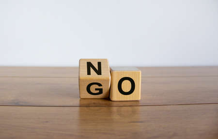 Fliped cube, changes the word NO to GO. Beautiful white background. Copy space.