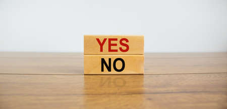 Wood blocks with words 'yes, no' on wooden table. Beautiful white background, copy space. Business concept.