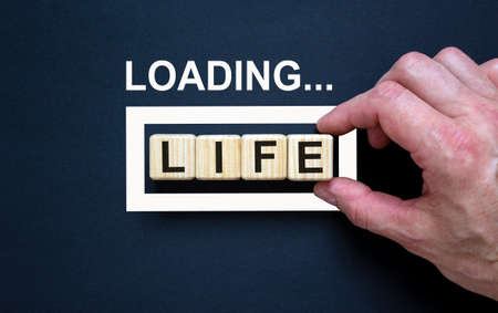 Loading word 'life' with hand putting wood cube in progress bar. Business concept.