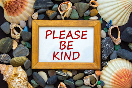Wooden picture frame with inscription 'please be kind' on beautiful black background. Sea stones and seashells. Concept.