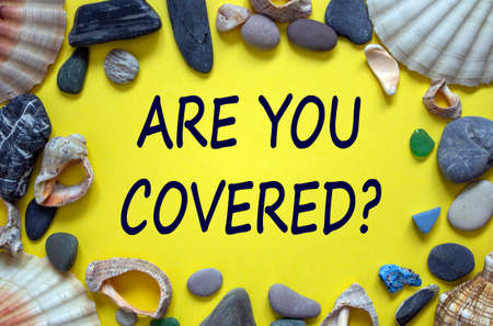 Text 'are you covered' on a beautiful yellow background. Sea stones and seashells. Travel insurance concept.