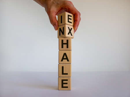 Inhale, Exhale concept. Hand turns cubes and changes the word 'INHALE' to 'EXHALE'. Beautiful white background. Copy space.