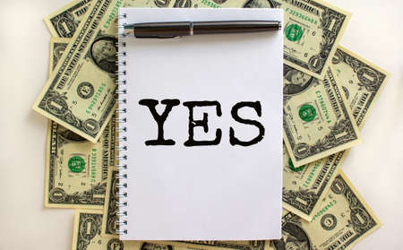 White note with word 'yes' on beautiful background from dollar bills. Metalic pen. Concept. Copy space.