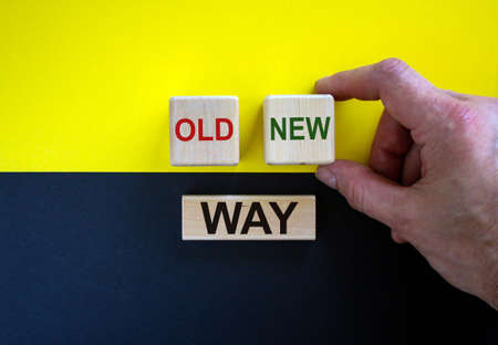 Businessman holds a cubes with word 'new'. Wooden cubes with words 'old way'. Beautiful yellow and black background. Copy space. Concept of new way choice. Stock fotó