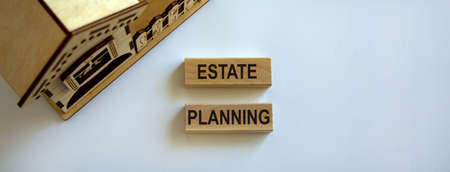 Wooden blocks form the words 'estate planning' near miniature house. Beautiful white background, copy space. Business concept.