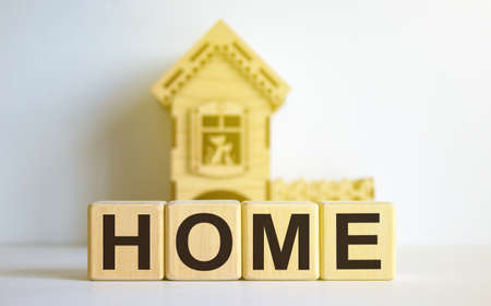 Cubes form the word 'home' in front of a miniature house. Warm light. Beautiful white background. Business concept. Copy space. Banco de Imagens