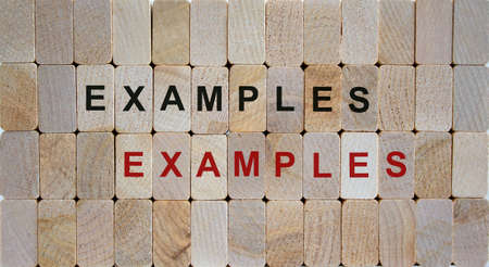 Wooden blocks form the words 'examples, examples'. Beautiful wooden background.