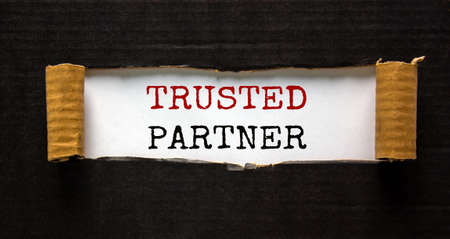 The word 'trusted partner' appearing behind torn black paper. Beautiful background. Business concept.