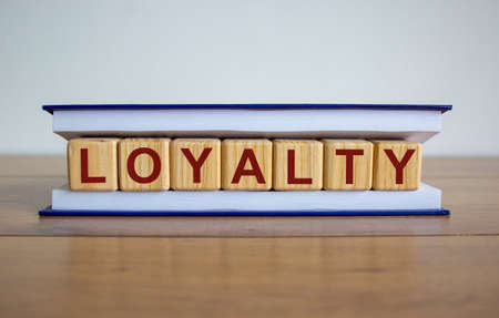 Concept word 'loyalty' on wooden cubes between pages of a book on a beautiful wooden table. White background. Business concept.