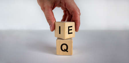 Hand flips a cube and changes the expression 'IQ' to 'EQ'. Beautiful white background. Concept. Copy space.
