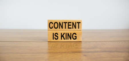 Wooden blocks form the text 'content is king' on beautiful wooden table, white background. Business concept, copy space.