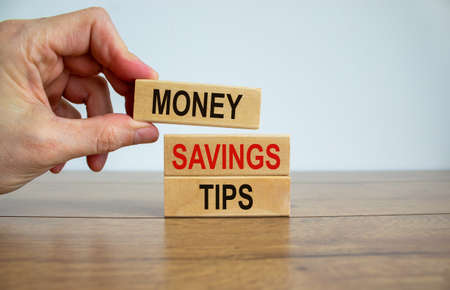 Male hand placing a block with word 'money' on top of a blocks with words 'money savings tips'. Beautiful wooden table, white background. Copy space. Business concept.