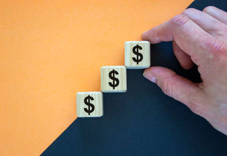 Business concept growth success process. Wood blocks with dollar sign stacking as step stair on paper peach and black background, copy space. Male hand.
