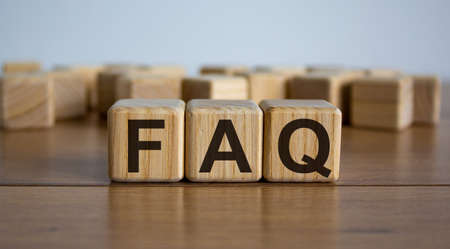 Concept word 'FAQ' on cubes on a beautiful wooden table. White background. Business concept.