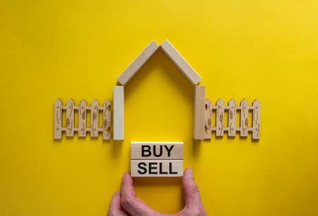 Model of a wooden house. Words 'buy, sell' on wooden blocks. Male hand, wooden fence. Copy space. Business concept. Beautiful yelllow background.