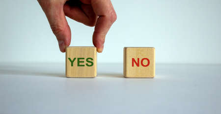 Hand making a choice between two cubes with 'Yes' and 'No' words on beautiful white background. Business concept.