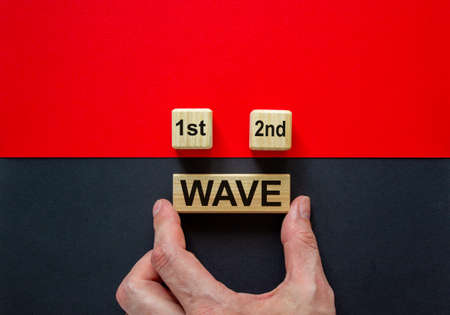 Symbol for a second wave of the corona virus. Hand holds cube with words '1st, 2nd, wave'. Copy space. Beautiful black and red background. 免版税图像