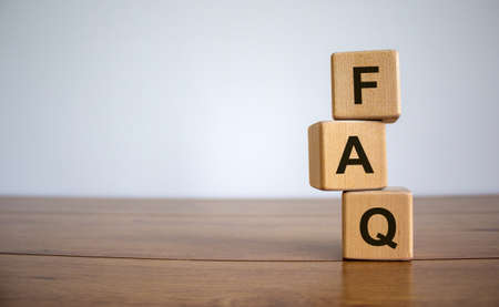 Concept word 'FAQ' on cubes on a beautiful wooden table. White background. Business concept, copy space.