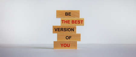 Concept of building success foundation. Wooden blocks on the stack of wooden blocks. Text 'be the best version of you'. Beautiful white background, copy space. 免版税图像