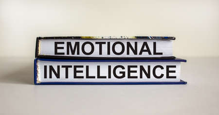 Books with text 'emotional intelligence' on beautiful white table. White background. Business concept. Copy space.