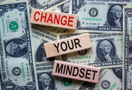 Wooden blocks form the text 'change your mindset' on beautiful background from dollar bills. Concept.